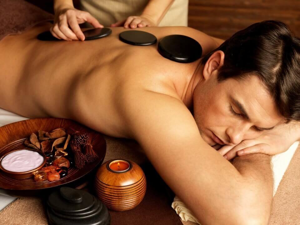 גבר מתפנק בעיסוי באבנים חמות וכאבי הגב פשוט עוברים